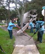 Workers smoothing out concrete
